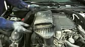 servicing : A man in gloves gently pulls out the air filter for replacement. He holds the device to protect the engine dust and dirt while driving on the road with both hands.
