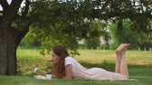 Young woman lying and reading a book under tree Stock Footage