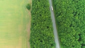enrolamento : Aerial flight over the lorries driving along the road surrounded by forest. 4K.