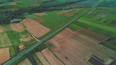 Beautiful landscape and village aerial with blue sky and clouds, a road, farmland and colorful fields. 4K.