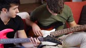 friends : Two casual guys posing on sofa and playing electric guitar and bass in band.