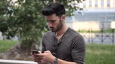 telefones : Young dark haired man standing in modern city setting, using smartphone to send text message or surfing the internet