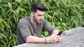 brim : Trendy handsome young man using cell phone to watch a video, while sitting on wood bench in urban environment