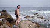 Handsome muscular young man standing on a rocky beach, relaxed, shirtless, wearing bathing suit Stock Footage
