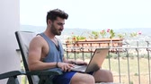 Waist Up Profile of Attractive Man with Dark Hair, Sitting with Laptop Computer Working or on His Start-up Business