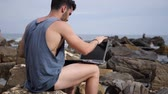 plavky : Young handsome man working on laptop computer, typing on keyboard while at the beach in front of the sea Dostupné videozáznamy