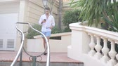 merdiven : Attractive fit athletic young man standing outdoor in elegant city setting on marble stairs, wearing white shirt in Montecarlo, Monaco on the French Riviera Stok Video