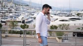не : Athletic man in white shirt at the seaside in Montecarlo, Monacos harbor, using cell phone to call someone with the sea behind him