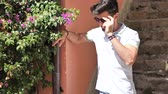 perfumy : Handsome young man in garden smelling beautiful flowers in a sunny day Wideo