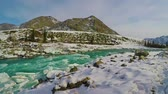 zúzmara : Spring high water on the Katun River, Altai Mountains, Siberia, Russia. Snow and ice on the river bank. Turquoise water and blue sky. Slow motion.