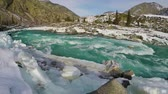 Spring high water on the Katun River, Altai Mountains, Siberia, Russia. Snow and ice on the river bank. Turquoise water and blue sky. Slow motion.