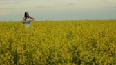рапсовое : A beautiful young girl dressed in a blue dress walks thoughtfully across a field of yellow flowers. He touches flowers with his hands. Smiles and laughs Стоковые видеозаписи