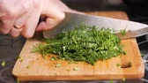 Cutting dill. Female hands cut board with wooden cutting board. Close-up Wideo