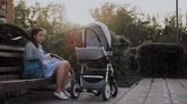 enfermagem : A girl sits on a park bench and rocks the baby