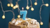 gonfler : Birthday cake with 7 number candle on blue backgraund. Candles blow out. Slow motion and close-up