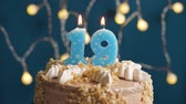 výrazný : Birthday cake with 19 number candle on blue backgraund. Candles blow out. Slow motion and close-up