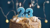 výrazný : Birthday cake with 23 number burning candle on blue backgraund. Candles blow out. Slow motion and close-up view