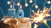 datum : Birthday cake with 50 number candle and sparkler on blue backgraund. Slow motion and close-up view