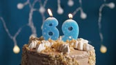 výrazný : Birthday cake with 69 number burning candle on blue backgraund. Candles blow out. Slow motion and close-up view
