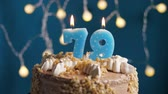 výrazný : Birthday cake with 79 number burning candle on blue backgraund. Candles blow out. Slow motion and close-up view