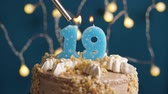 gyertya : Birthday cake with 19 number burning candle by lighter on blue backgraund. Candles are set on fire. Slow motion and close-up view Stock mozgókép