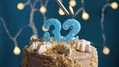 isqueiro : Birthday cake with 32 number burning candle by lighter on blue backgraund. Candles are set on fire. Slow motion and close-up view Vídeos