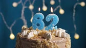 výrazný : Birthday cake with 62 number burning candle by lighter on blue backgraund. Candles are set on fire. Slow motion and close-up view