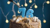 výrazný : Birthday cake with 76 number burning candle by lighter on blue backgraund. Candles are set on fire. Slow motion and close-up view