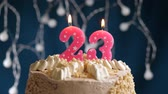 gonfler : Birthday cake with 23 number pink burning candle on blue backgraund. Candles blow out. Slow motion and close-up view
