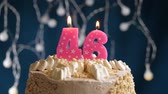 gonfler : Birthday cake with 46 number pink burning candle on blue backgraund. Candles blow out. Slow motion and close-up view Vidéos Libres De Droits