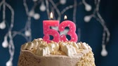 gonfler : Birthday cake with 53 number pink burning candle on blue backgraund. Candles blow out. Slow motion and close-up view