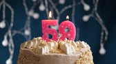gonfler : Birthday cake with 59 number pink burning candle on blue backgraund. Candles blow out. Slow motion and close-up view Vidéos Libres De Droits