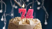 isqueiro : Birthday cake with 74 number burning by lighter pink candle on blue backgraund. Candles are set on fire. Slow motion and close-up view