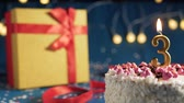 White birthday cake number 3 golden candles burning by lighter, blue background with lights and gift yellow box tied up with red ribbon. Close-up Wideo