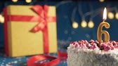 White birthday cake number 6 golden candles burning by lighter, blue background with lights and gift yellow box tied up with red ribbon. Close-up Wideo