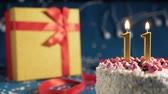White birthday cake number 11 golden candles burning by lighter, blue background with lights and gift yellow box tied up with red ribbon. Close-up Wideo