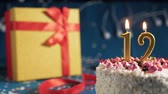 White birthday cake number 12 golden candles burning by lighter, blue background with lights and gift yellow box tied up with red ribbon. Close-up