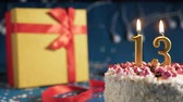 White birthday cake number 13 golden candles burning by lighter, blue background with lights and gift yellow box tied up with red ribbon. Close-up Wideo