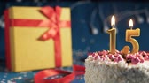White birthday cake number 15 golden candles burning by lighter, blue background with lights and gift yellow box tied up with red ribbon. Close-up