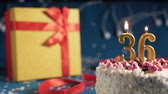 isqueiro : White birthday cake number 36 golden candles burning by lighter, blue background with lights and gift yellow box tied up with red ribbon. Close-up