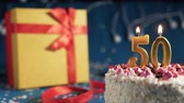 White birthday cake number 50 golden candles burning by lighter, blue background with lights and gift yellow box tied up with red ribbon. Close-up Wideo