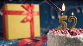 White birthday cake number 52 golden candles burning by lighter, blue background with lights and gift yellow box tied up with red ribbon. Close-up Wideo