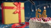 White birthday cake number 64 golden candles burning by lighter, blue background with lights and gift yellow box tied up with red ribbon. Close-up Wideo