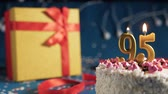 White birthday cake number 95 golden candles burning by lighter, blue background with lights and gift yellow box tied up with red ribbon. Close-up Wideo
