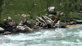 crashed : Wreck of an old Lada besides a raging river.