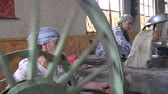 steamed : Women turn a spinning wheel to produce silk in a traditional way. Stock Footage