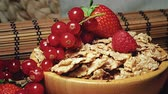 müsli : Strawberries raspberries currants cereal grains on wooden cutting board Stok Video