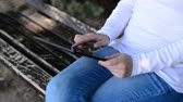 aletsiz : Woman holds and taps digital tablet computer on a wooden bench in the park. Handheld or free hand camera 1920x1080 full hd footage. Stok Video