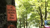 t��o : No vehicles beyond this point sign attached to a tree in camping zone, car passing in out of focus background, handheld camera
