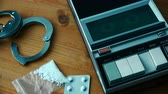 aresztowany : Drug related police arrest concept, top view with tape player playing cassette with suspects statement during police interrogation.